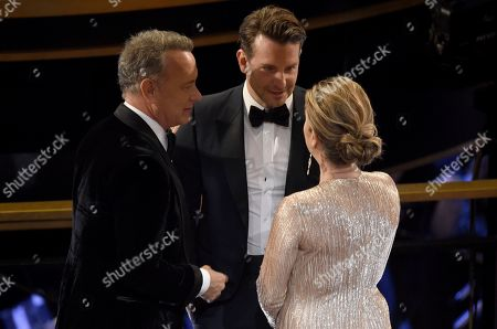 Tom Hanks, Bradley Cooper, Rita Wilson. Tom Hanks, from left, Bradley Cooper and Rita Wilson speak in the audience at the Oscars, at the Dolby Theatre in Los Angeles