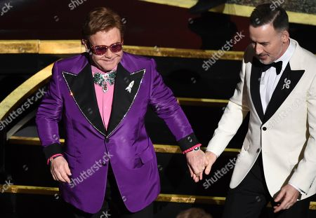 Sir Elton John, David Furnish. Sir Elton John, left, and David Furnish walk off stage at the Oscars, at the Dolby Theatre in Los Angeles