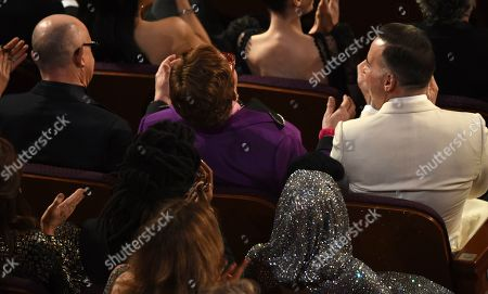 """David Furnish, Bernie Taupin, Sir Elton John. Bernie Taupin, from left, Sir Elton John and David Furnish react in the audience before accepting the award for best original song for """"(I'm Gonna) Love Me Again"""" from """"Rocketman"""" at the Oscars, at the Dolby Theatre in Los Angeles"""