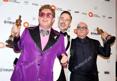 Sir Elton John, from left, David Furnish, and Bernie Taupin celebrate Sir Elton John and Bernie Taupin winning an Academy Award as they arrive at the 2020 Sir Elton John AIDS Foundation Oscar Viewing Party, in West Hollywood, Calif