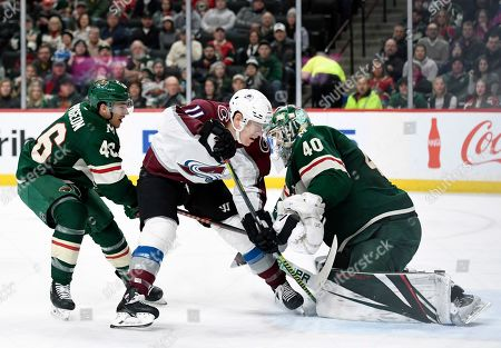 Minnesota Wild goaltender Devan Dubnyk (40) stop s shot by Colorado Avalanche's Matt Calvert (11) with help from Minnesota Wild's Jared Spurgeon (46) during the second period of an NHL hockey game, in St. Paul, Minn. Spurgeon was called for a penalty on the play