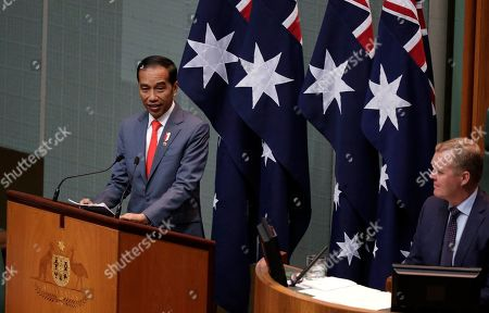 Indonesia's President Joko Widodo, left, address the Australian Parliament in Canberra, as the speaker of the house, Tony Smith, right, listens . Widodo is on a two-day visit to Canberra, his fourth visit to Australia