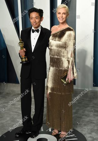 """Stock Image of Kazuhiro Tsuji, Charlize Theron. Kazuhiro Tsuji, winner of the award for best makeup and hairstyling for """"Darkest Hour,"""" left, and Charlize Theron arrive at the Vanity Fair Oscar Party, in Beverly Hills, Calif"""