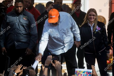 The President of Venezuela, Nicolas Maduro (C), along with his wife Cilia Flores (R), greets supporters during a march in which sympathizers of the ruling party and workers of the Conviasa airline participate in rejection of the sanctions that the United States imposed on this state company, in Caracas, Venezuela, 10 February 2020. The Venezuelan government announced on 08 February that it will denounce before international instances the recent sanction issued by the Administration of the US President Donald Trump, against its state airline, while calling the measure a 'big mistake' political.
