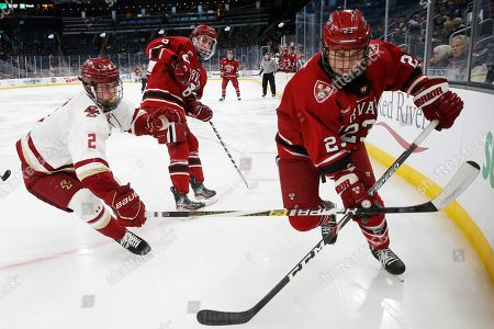 Baker Shore, Michael Karow. Boston College's Michael Karow (2) and Harvard's Baker Shore (23) battle for the puck during the second period of the Beanpot Tournament consolation NCAA college hockey game in Boston