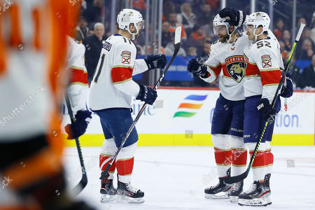 MacKenzie Weegar, Aaron Ekblad, Jonathan Huberdeau. Florida Panthers' MacKenzie Weegar (52), Aaron Ekblad (5) and Jonathan Huberdeau (11) celebrate after a goal by Weegar during the first period of an NHL hockey game against the Philadelphia Flyers, in Philadelphia