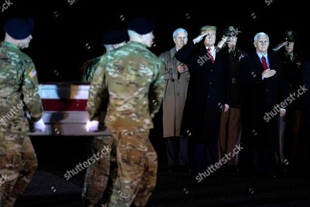 President Donald Trump salutes with Vice President Mike Pence as a U.S. Army carry team moves a transfer case containing the remains of Sgt. 1st Class Antonio Rodriguez, of Las Cruces, N.M., at Dover Air Force Base, Del. According to the Department of Defense both Rodriquez and Sgt. 1st Class Javier Gutierrez, of San Antonio, Texas, died Saturday, Feb. 8, during combat operations in Afghanistan
