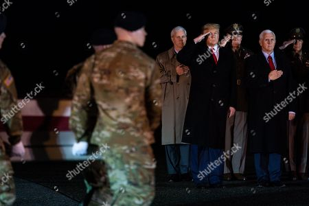 President Donald Trump watches as a U.S. Army carry team moves a transfer case containing the remains of Sgt. 1st Class Javier Gutierrez, of San Antonio, Texas, at Dover Air Force Base, Del. According to the Department of Defense both died Saturday, Feb. 8, during combat in Afghanistan