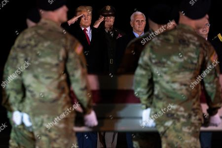 President Donald Trump watches as a U.S. Army carry team moves a transfer case containing the remains of Sgt. 1st Class Javier Gutierrez, of San Antonio, Texas, at Dover Air Force Base, Del. According to the Department of Defense both Gutierrez and Sgt. 1st Class Antonio Rodriguez, of Las Cruces, N.M., died Saturday, Feb. 8, during combat operations in Afghanistan