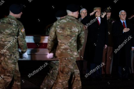 President Donald Trump watches as a U.S. Army carry team moves a transfer case containing the remains of Sgt. 1st Class Antonio Rodriguez, of Las Cruces, N.M., at Dover Air Force Base, Del. According to the Department of Defense both Rodriquez and Sgt. 1st Class Javier Gutierrez, of San Antonio, Texas, died Saturday, Feb. 8, during combat operations in Afghanistan