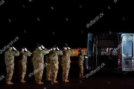 A U.S. Army carry team salutes the transfer case's containing the remains of Sgt. 1st Class Javier Gutierrez, of San Antonio, Texasa and Sgt. 1st Class Antonio Rodriguez, of Las Cruces, N.M., at Dover Air Force Base, Del. According to the Department of Defense both died Saturday, Feb. 8, during combat in Afghanistan