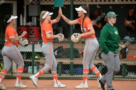 Sam Houston State pitcher Karina Sanchez, second from right, is congratulated by teammate Megan McDonald after completing an inning during an NCAA softball game against George Mason in Deland, Fla