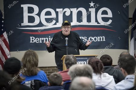 Film director Michael Moore sits in for Sanders during an election campaign meeting.