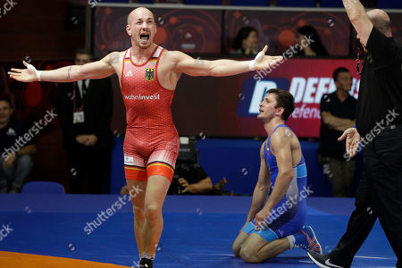 Germany's Frank Staebler, left, celebrates after winning against Russia's Adam Kurak during the semi-final of the 72Kg category of the men's Greco-Roman wrestling at the European Wrestling Championships in Ostia, Italy