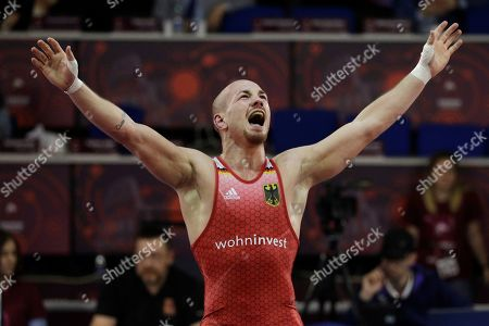 Germany's Frank Staebler celebrates after winning against Russia's Adam Kurak during the semi-final of the 72Kg category of the men's Greco-Roman wrestling at the European Wrestling Championships in Ostia, Italy