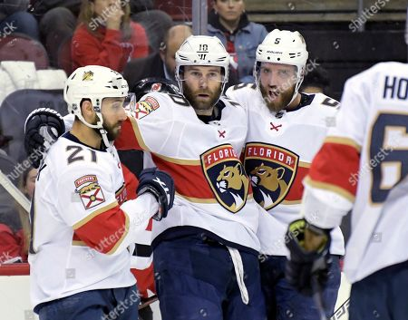 Florida Panthers right wing Brett Connolly (10) celebrates his goal with Vincent Trocheck (21) and Aaron Ekblad (5) during the first period of an NHL hockey game against the New Jersey Devils, in Newark, N.J