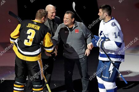 Mike Eruzione, center right, captain of the 1980 U.S Men's Hockey team, and assistant coach Craig Patrick, center left, participate in a ceremonial face off between Pittsburgh Penguins' Jack Johnson (3) and Tampa Bay Lightning's Pat Maroon (14) to commemorate the 40th anniversary of the United States win over the Soviet Union during the 1980 Winter Olympics before an NHL hockey game between the Pittsburgh Penguins and the Tampa Bay Lightning in Pittsburgh, . The Lightning won in overtime 2-1