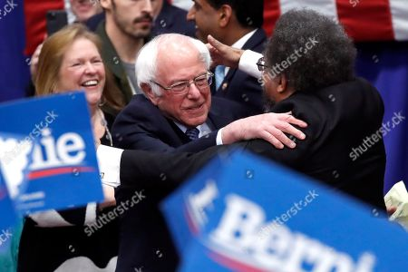 Democratic presidential candidate Sen. Bernie Sanders, I-Vt., hugs Cornel West as Jane O'Meara Sanders watches at a primary night election rally in Manchester, N.H