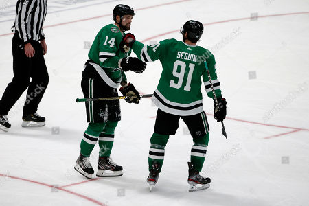 Dallas Stars left wing Jamie Benn (14) gets congratulated on his hat trick against the Carolina Hurricanes by center Tyler Seguin (91) during the third period of an NHL hockey game in Dallas, . Dallas defeated Carolina 4-1