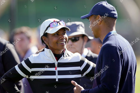 Former Secretary of State Condoleezza Rice, left, talks to Tiger Woods on the 17th hole during the Genesis Invitational pro-am golf event at Riviera Country Club, in the Pacific Palisades area of Los Angeles