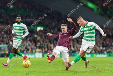 Leigh Griffiths of Celtic shoots at goal under pressure from Michael Smith of Heart of Midlothian