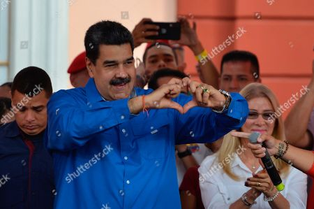 Stock Picture of Venezuela's Nicolas Maduro, accompanied by first lady Cilia Flores, flashes a heart-hand symbol at supporters during an event at the Miraflores Presidential Palace to mark Youth Day, in Caracas, Venezuela