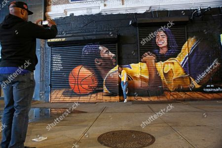 """James Lawson pauses to take a cellphone photo of Naimah Pitts, who wears a LeBron James jersey as she poses in front of a mural painted in memory of former Los Angeles Lakers star Kobe Bryant and his daughter Gianna, along with the names of the seven other victims of the Jan. 26 helicopter crash in California, in New York. The mural was painted last week by Efren Andaluz III, who goes by """"Andaluz the Artist."""" Both Pitts and Lawson live in Keyport, N.J. The mural is located across the street from the Barclays Center arena in Brooklyn"""