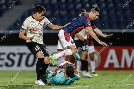 Stock Picture of Oscar Ramon Ruiz (top) of Cerro Porteno vies for the ball with Jose Carvallo (down) goalkeeper of Universitario during their Copa Libertadores soccer match between Cerro Porteno and Universitario de Deportes at the Nueva Olla stadium in Asuncion, Paraguay, 12 February 2020. The match was played without fans due a Conmebol's sanction after a riot late August 2019.