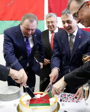 Swiss Federal Councillor and Foreign Minister Ignazio Cassis (2-R) cuts a cake with Belarusian Foreign Minister Vladimir Makei (L)  during the opening ceremony of the Swiss embassy in Minsk, Belarus, 13 February 2020. Ignazio Cassis is on his visit in Belarus, during which a Swiss embassy will be opened. Others in image are unidentified.