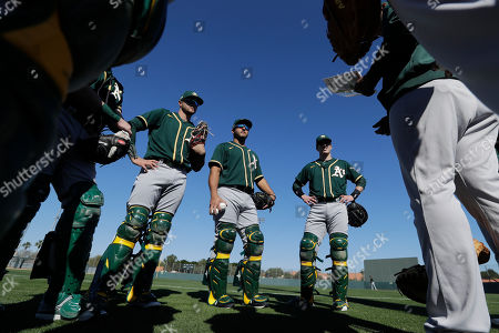 Oakland Athletics' Austin Allen, Carlos Perez, and Ronnie Freeman, from left, listen to instructions during spring training baseball practice, in Mesa, Ariz