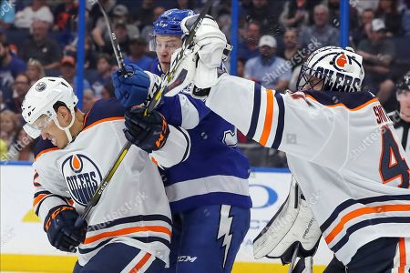Edmonton Oilers goaltender Mike Smith reaches out to make a save as Caleb Jones defends against Tampa Bay Lightning's Yanni Gourde during the second period of an NHL hockey game, in Tampa, Fla