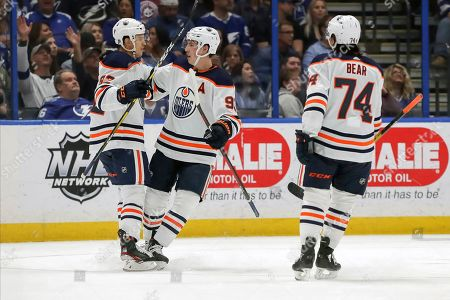 Edmonton Oilers' Caleb Jones, left, is congratulated by Ryan Nugent-Hopkins and Ethan Bear after scoring against the Tampa Bay Lightning during the second period of an NHL hockey game, in Tampa, Fla. The Lightning won 3-1