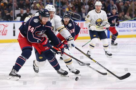 Buffalo Sabres forward Kyle Okposo (21) and Columbus Blue Jackets defenseman Vladislav Gavrikov (44) battle for the puck during the first period of an NHL hockey game, in Buffalo, N.Y