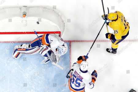 Stock Image of Craig Smith, Thomas Greiss, Johnny Boychuk. Nashville Predators right wing Craig Smith (15) bounces the puck off New York Islanders goaltender Thomas Greiss, left, of Germany, for a goal in the first period of an NHL hockey game, in Nashville, Tenn. Islanders' Johnny Boychuk (55) also defends