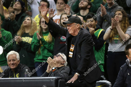 Oregon fan and Nike co-founder Phil Knight, center, acknowledges the crowd during the first half of an NCAA college basketball game between Oregon and Colorado in Eugene, Ore