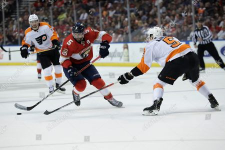 Florida Panthers defenseman Aaron Ekblad, left, and Philadelphia Flyers defenseman Philippe Myers (5) go for the puck during the first period of an NHL hockey game, in Sunrise, Fla