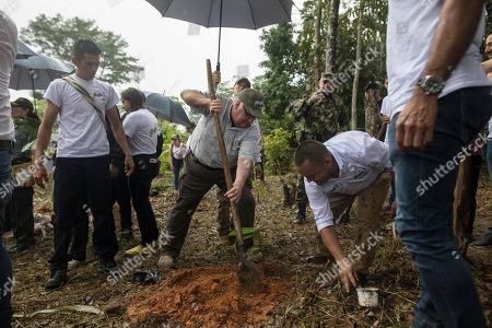 An assistant holds an umbrella over Howard Buffett as he plants a cocoa plant at a farm in La Gabarra, Colombia, . The eldest son of billionaire investor Warren Buffett has crisscrossed the world giving away part of his father's fortune to promote food security, conflict mitigation and public safety. His latest gamble is one of the most daunting yet: helping Colombia kick its cocaine curse