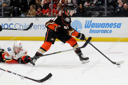 Calgary Flames defenseman Michael Stone, left, trips Anaheim Ducks right wing Troy Terry during the second period of an NHL hockey game in Anaheim, Calif