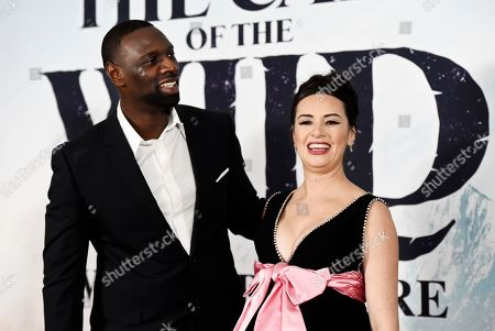 """Omar Sy, Cara Gee. Omar Sy, left, and Cara Gee, cast members in """"The Call of the Wild,"""" pose together at the premiere of the film at the El Capitan Theatre, in Los Angeles"""
