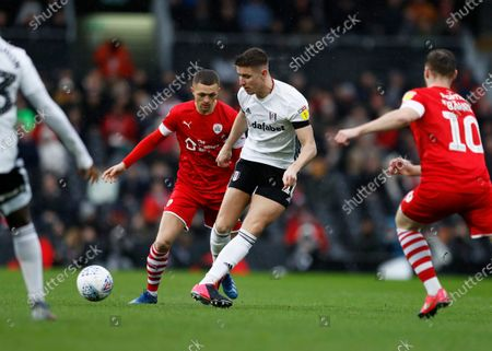 15th February 2020; Craven Cottage, London, England; English Championship Football, Fulham versus Barnsley; Tom Cairney of Fulham passing the ball into midfield while being marked by Jordan Williams and Mike-Steven Bahre of Barnsley