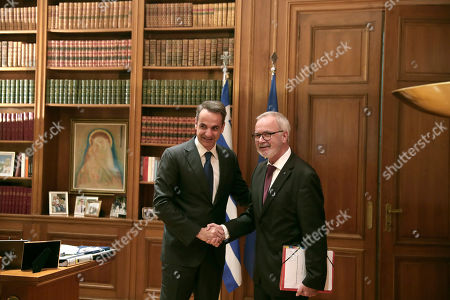 Kyriakos Mitsotakis, Werner Hoyer. Greek Prime Minister Kyriakos Mitsotakis, left, shakes hands with President of the European Investment Bank Werner Hoyer during their meeting in Athens, on