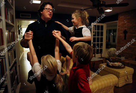 Catholic Priest, husband and dad Joshua Whitfield plays with three of his four children Maggie, 9, Peter, 8, and Zoe-Catherine, 5, at their home in north Dallas