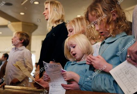 The family of Catholic Priest Joshua Whitfield, from left, Peter, 8, his wife, Alli, and daughters Maggie, 9, Bernadette, 4, and Zoe-Catherine, 5, stand together in a pew during Sunday Mass at St. Rita Catholic Community in Dallas. In 2009 the Whitfields, who were Episcopalian, converted to Catholicism and Josh Whitfield was ordained as a priest less than three years later