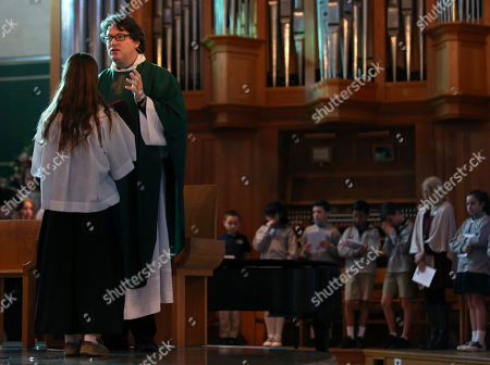 Natalie Kricken, student at St. Rita Catholic School, left, holds the Bible in front of converted Catholic Priest Joshua Whitfield during a weekly student Mass at St. Rita Catholic Community in Dallas. Whitfield came to the Catholic church as a former Episcopalian pastor, a husband and soon-to-be dad