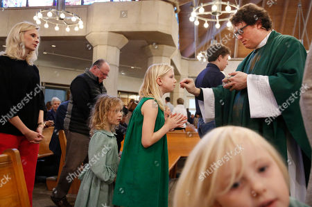 The Whitfield family, wife Alli, left, daughters Zoe-Catherine, 5, second from left, and Maggie, 9, second from right, receive communion from their dad and husband, The Rev. Joshua Whitfield, right, during Sunday Mass at St. Rita Catholic Community in Dallas. In 2009 the Whitfields, who were Episcopalian, converted to Catholicism