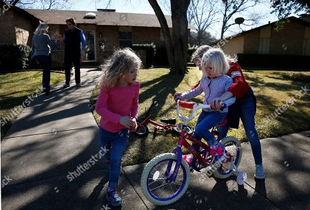 Alli Whitfield, left, high-fives husband and Catholic Priest Joshua, as their three daughters Zoe-Catherine, 5, Bernadette, 4, and Maggie, 9, ride bikes outside of their home in north Dallas