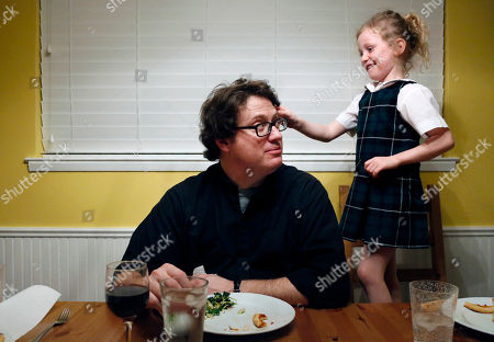 Converted Catholic Priest Joshua Whitfield of north Dallas, left, looks up at his daughter Zoe-Catherine, 5, who stands on a kitchen chair pressing a pink butterfly clip into his hair during dinner in north Dallas