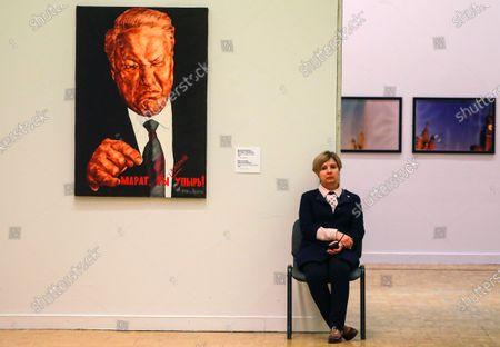 Stock Image of A gallery worker sits near the artwork 'Marat, you are a Greedy Ghoul' by Dmitry Vrubel and Viktoria Timofeeva depicting former Russian President Boris Yeltsin in the exhibition of works which Russian contemporary art collector and gallerist Marat Gelman donated to the State Tretyakov Gallery in Moscow, Russia, 14 February 2020. Gelman Gallery, one of the first private galleries in Moscow, was founded in 1990.