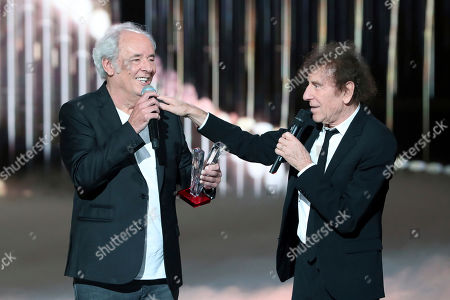 French singer and songwriter Maxime Le Forestier, left, receives a special honour award by French singer and songwriter Alain Souchon during the 35th Victoires de la Musique, the annual French music awards ceremony, in Paris