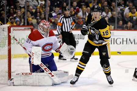 Pittsburgh Penguins' Jared McCann (19) gets out of the way of a shot in front of Montreal Canadiens goaltender Carey Price (31) during the second period of an NHL hockey game in Pittsburgh, . The Penguins won 4-1